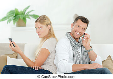 Couple both using their phones on the sofa