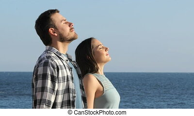 Couple breathing fresh air on the beach - Side view portrait...