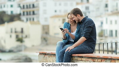 Couple browsing on phone on a ledge