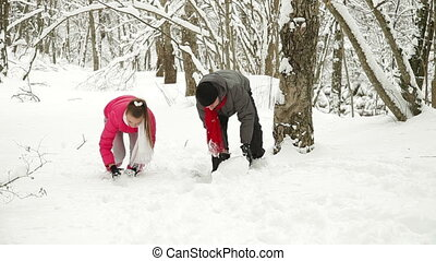 Couple Building Snowman In Forest