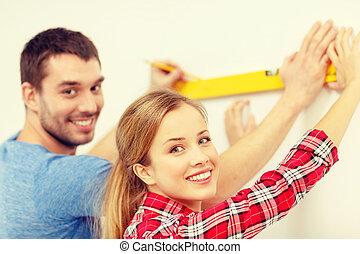 couple building using spirit level to measure - repair, ...