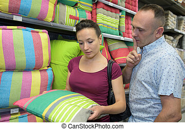 couple buying fluffy pillow in home textile store
