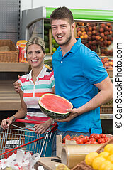 Couple Buying Fruits And Vegetables In Supermarket -...