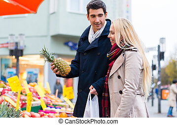 Couple buying groceries on farmers market stand