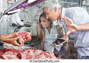Couple Buying Meat At Butchery - Mature couple buying fresh ...
