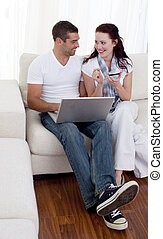 Couple buying online with a credit card on sofa