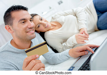 couple buying online with a laptop and credit card