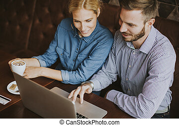 Couple buying online with credit card and laptop in a coffee shop
