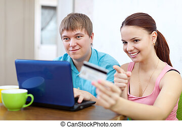 couple buying online with credit card at home
