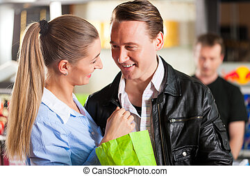 Couple buying popcorn embracing at theatre - Young couple...