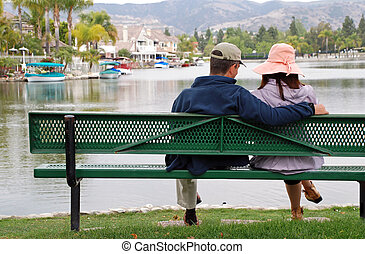 Couple by the Lake - Man - A couple sit on a bench by a...