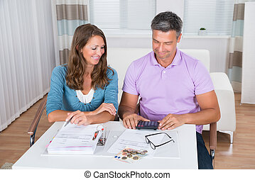 Couple Calculating Bills At Home
