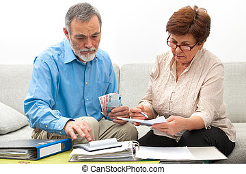 couple calculating home finances - senior couple worrying ...