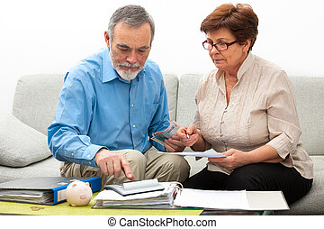 couple calculating home finances - senior couple worrying...