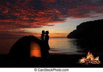 Couple camping and kissing on the beach with red sky sunset background
