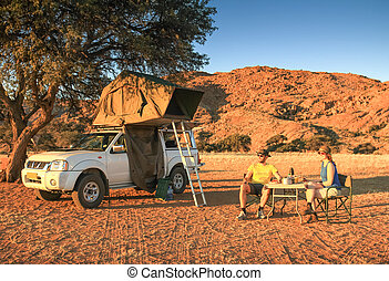 Couple camping in desert having dinner. Orange sunset sunrise light.