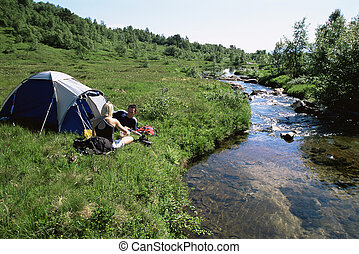 Couple camping next to stream