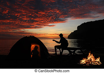 Couple camping with guitar and campfire on the beach