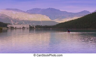 Couple Canoe Across Mountain Lake - Couple in canoe travels...