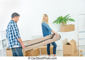 couple carrying a carpet