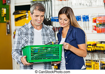 Couple Carrying Basket Full Of Tools In Store