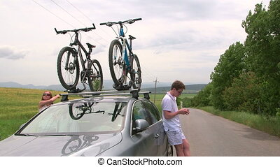Couple carrying bicycles on the roof of his car