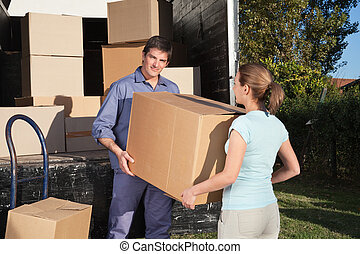 Couple carrying box into the truck while moving into new...