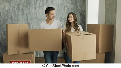 Couple Carrying Boxes Into New Home On Moving Day. Young family moving in new home
