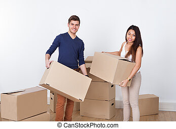 Couple Carrying Cardboard Boxes At New Home