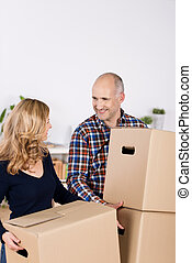 Couple Carrying Cardboard Boxes While Looking At Each Other