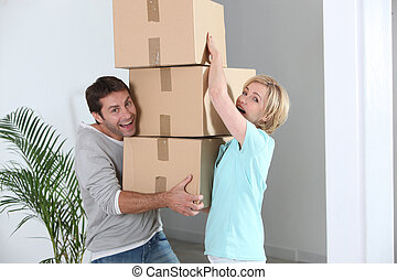 Couple carrying pile of boxes