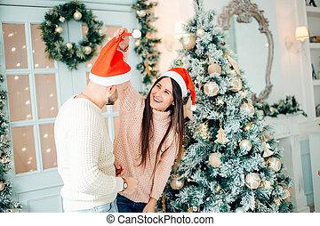 Couple celebrating Christmas together at Christmas tree background