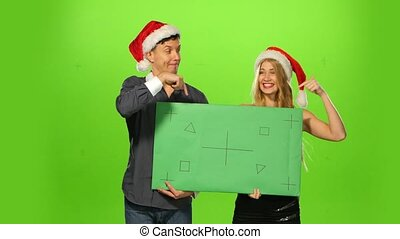Couple celebrating new year eve. green screen, blank sign -...