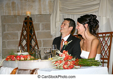 Couple Ceremony - Bride and groom sitting at table at...