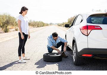 Couple changing wheel on a roadside
