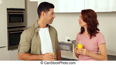 Couple chatting and drinking orange juice at home in the...