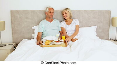 Couple chatting and having breakfast in bed at home in...