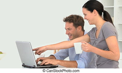 Couple chatting on the laptop in the kitchen