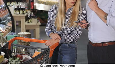 Couple check what they buy by the list in smartphone