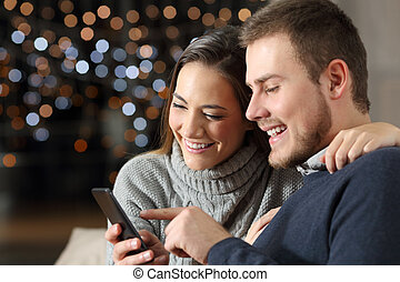 Couple checking phone content in winter at home