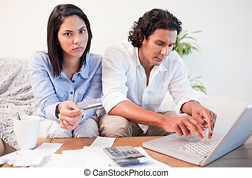 Couple checking their bank accounts online in the living room