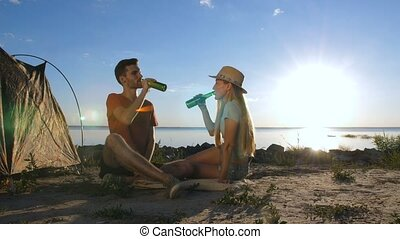 Couple cheering and drinking beer during camping - Young...