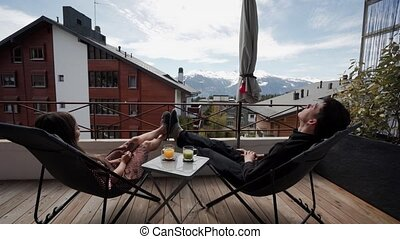 Couple chilling on open terrace with amazing mountains view. They play with their feet in warm slippers. Happy family relaxing together. Funny moments