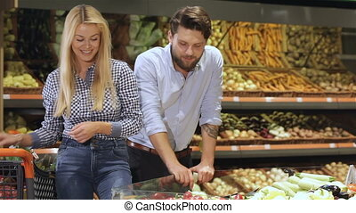 Couple choose bell peppers at the supermarket