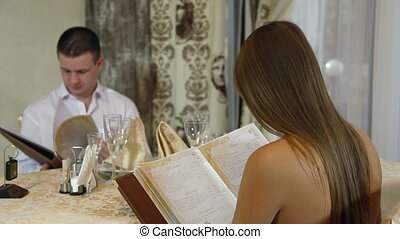 couple chooses dishes from menu
