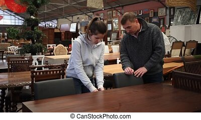 Woman and man consumer choosing table furniture store