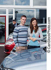 Couple choosing a car in a dealership