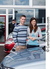 Couple choosing a car in a dealership