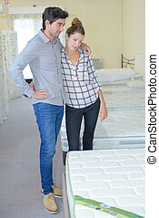 couple choosing bed in a furniture shop