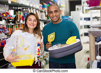 Couple choosing bird cage and cat accessories at pet store